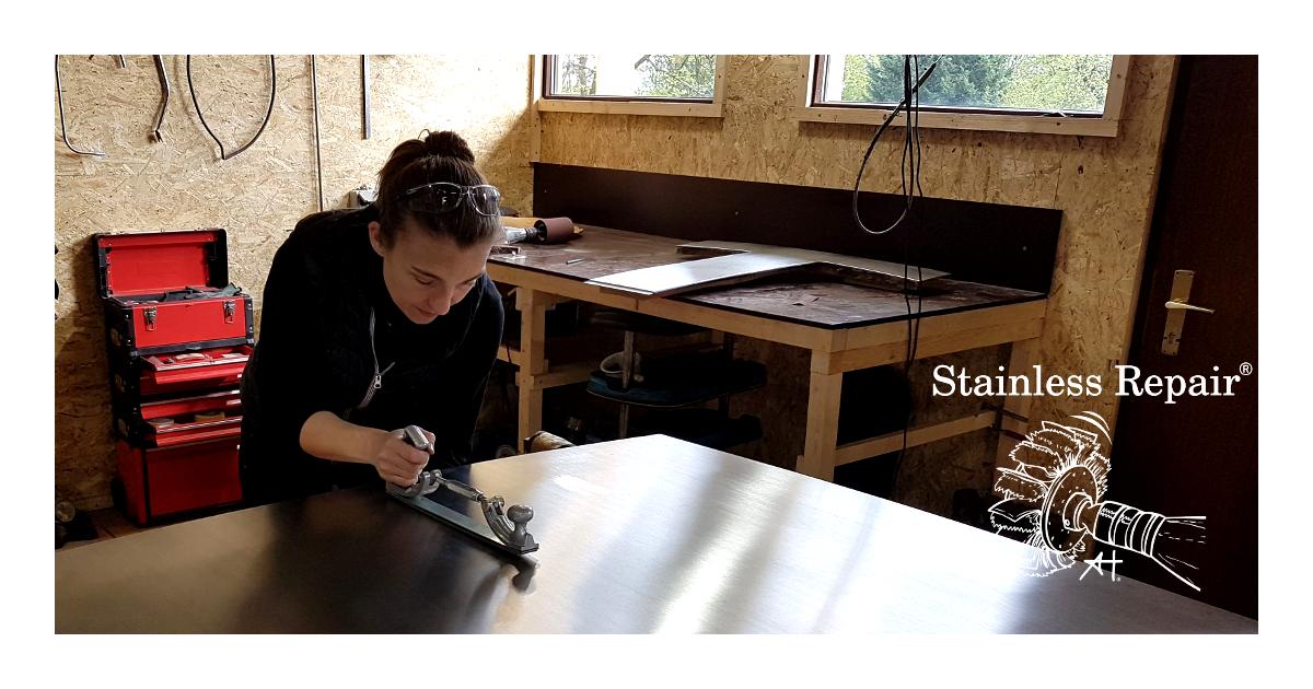 Anna Hirt arbeitet an der einer DeLorean DMC12 Kofferraumhaube. Dellen und Kratzer werden entfernt.